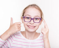 Den lyckliga blonda barnflickan i exponeringsglas som visar tummar gör en gest upp Royaltyfri Foto