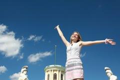 Den lyckliga blonda kvinnan med beväpnar lyftt Arkivbild
