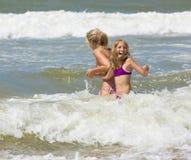Den lyckliga blonda modern och dottern spelar bland vågor av havet Arkivbilder
