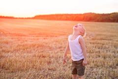 Den lyckliga blonda pojken st?r med hans huvud upp p? ett mejat vetef?lt skjuten solnedg?ngtid f?r exponering long arkivbilder