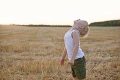 Den lyckliga blonda pojken st?r med hans huvud upp p? ett mejat vetef?lt skjuten solnedg?ngtid f?r exponering long royaltyfria bilder