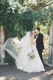 Den lyckliga den bröllopparbruden och brudgummen som poserar i ett botaniskt, parkerar arkivfoto