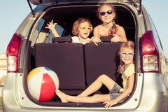 Den lyckliga brodern och hans två systrar sitter i bilen Fotografering för Bildbyråer