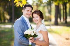 Den lyckliga bruden, brudgummen som ser camers i gräsplan, parkerar Kyssa och att le och att skratta vänner i bröllopdag förbunde Fotografering för Bildbyråer