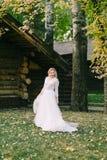 Den lyckliga bruden med lockigt blont hår poserar bredvid trähuset tillbaka Lantligt bröllop Royaltyfria Bilder