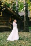 Den lyckliga bruden med lockigt blont hår poserar bredvid trähuset tillbaka Lantligt bröllop Royaltyfria Foton