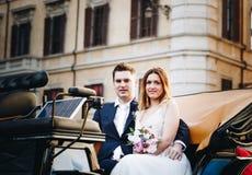 Den lyckliga bruden och brudgummen i härlig vagn på bröllop går arkivbild