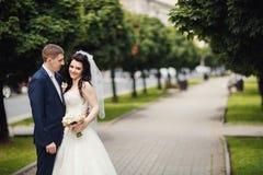 Den lyckliga bruden och brudgummen i skuggig gränd på bröllop går Royaltyfria Bilder