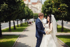 Den lyckliga bruden och brudgummen i skuggig gränd på bröllop går Arkivfoton