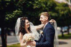 Den lyckliga bruden och brudgummen i solig stadsgränd på bröllop går Royaltyfri Fotografi