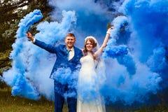 Den lyckliga bruden och brudgummen med blå rök bombarderar Royaltyfri Bild