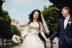 Den lyckliga bruden och brudgummen på den soliga gränden på bröllop går Fotografering för Bildbyråer
