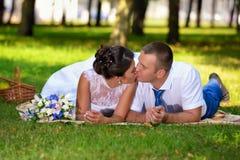Den lyckliga bruden och brudgummen på deras brölloplögner på gräset parkerar och kysser in Royaltyfria Bilder