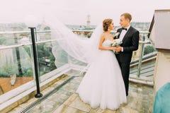 Den lyckliga bruden och brudgummen som kramar slappt på terrassen med cityscapebakgrund, vind som lyfter långt brud-, skyler Royaltyfri Foto