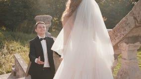Den lyckliga brudgummen kommer till bruden, smekningar och kysser sig på trappa stock video