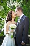 Den lyckliga brudgummen och den lyckliga bruden i fjäder arbeta i trädgården Royaltyfri Fotografi