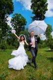 Den lyckliga brudgummen och den lyckliga bruden med paraplyet i sommar parkerar Arkivfoton