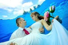 Den lyckliga brudgummen rymmer bruden i hans armar undervattens- i pölen och ser henne Arkivfoto
