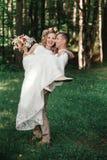 Den lyckliga brudgummen rymmer hans brud i hans armar Royaltyfria Foton