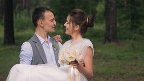 Den lyckliga brudgummen rymmer på händer den härliga bruden, slut upp lager videofilmer