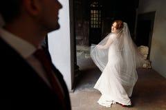 Den lyckliga brudgummen ser härlig blond bruddans i streen royaltyfri foto
