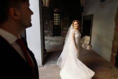 Den lyckliga brudgummen ser härlig blond bruddans i streen arkivbilder