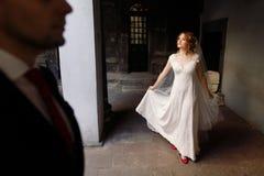 Den lyckliga brudgummen ser härlig blond bruddans i streen royaltyfria foton