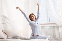 Den lyckliga brunettflickan i den ljusblå pajamaen sträcker hennes armar upp att sitta på markissängen bredvid fönstret i royaltyfri foto