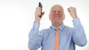 Den lyckliga businesspersonen Make Enthusiastic Winner gör en gest läsninggoda nyheter på mobil royaltyfria bilder