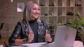 Den lyckliga caucasian blonda flickan sitter på skrivbordet och visar som tecken på kameran nära hennes dator som är avkopplad oc lager videofilmer