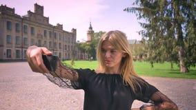 Den lyckliga caucasian kvinnan tar selfies, medan stå rak på gatan och le, forntida byggnader på lager videofilmer