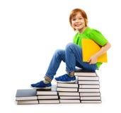 Den klyftiga pojken på hög av bokar Arkivbild