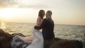 Den lyckliga charmiga nygifta personen som paret sitter på, vaggar och att krama och tala ömt på bakgrunden av havet under arkivfilmer