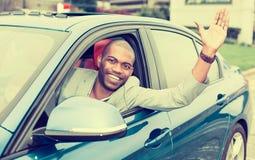 Den lyckliga chauffören för den unga mannen klibbade hans hand ut ur bilfönstret royaltyfria foton