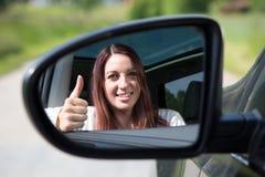 Den lyckliga chaufförvisningen tummar upp i spegeln Fotografering för Bildbyråer