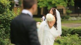 Den lyckliga den nygift personbruden och brudgummen i sommar parkerar Skämtsam brud som gör tecken åt hennes älska nya make arkivfilmer