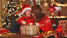 Den lyckliga det familjmodern och barnet packar julgåvor royaltyfri foto