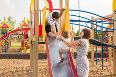 Den lyckliga det fria för pys i lekplats med hans föräldrar royaltyfria foton