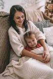 Den lyckliga dottern och en moder som skrattar på sängen arkivfoton