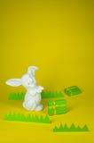Den lyckliga easter kaninen med gåvor och fejkar pappers- gräs Royaltyfri Fotografi
