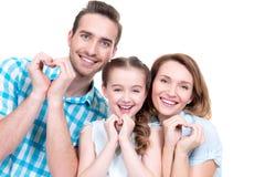 Den lyckliga europeiska familjen med barnet visar hjärtaformen Arkivfoto
