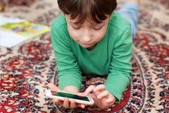 Pojke som armbågar med mobiltelefon arkivfoto