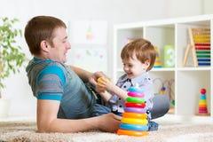 Den lyckliga fader- och barnsonen spelar tillsammans inomhus på Royaltyfri Fotografi