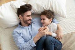 Den lyckliga fadern har gyckel som spelar med den lilla sonen royaltyfri fotografi