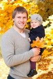 Den lyckliga fadern med dottern i höst parkerar arkivfoton