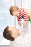 Den lyckliga fadern med förtjusande behandla som ett barn Fotografering för Bildbyråer