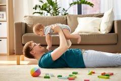 Den lyckliga fadern med litet behandla som ett barn sonen som hemma spelar arkivbilder