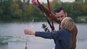 Den lyckliga fadern med sonen fiskar lager videofilmer