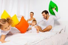 Den lyckliga fadern, modern och ungar spelar med kuddar Arkivfoto