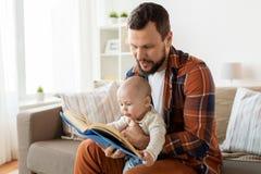 Den lyckliga fadern och behandla som ett barn lite pojken med den hemmastadda boken Royaltyfri Bild